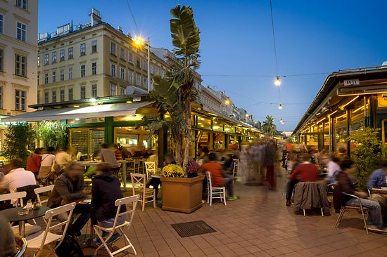 Bustling scene in the pubs and cafes at Naschmarkt, exterior shot with people