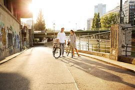 Two cyclists by the Danube Canal