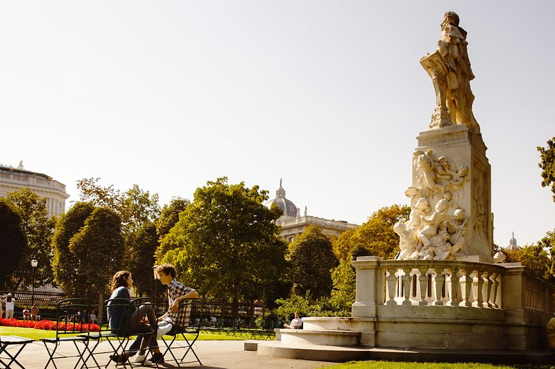 Two people sitting in the sun in the Burggarten by the statue of Mozart.