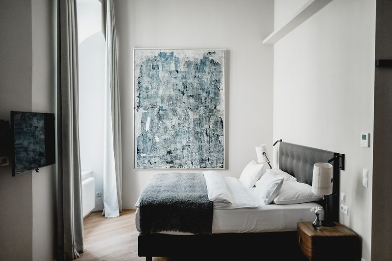 Hotel room with a painting by Elisa Alberti