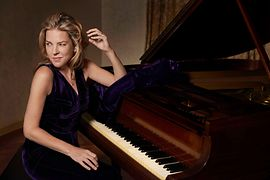 Singer Diana Krall sitting at a grand piano.