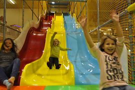 Family Fun, three girls on a big coloured slide